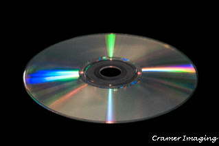 Stock photograph of a CD or compact disk on a black background by Cramer Imaging