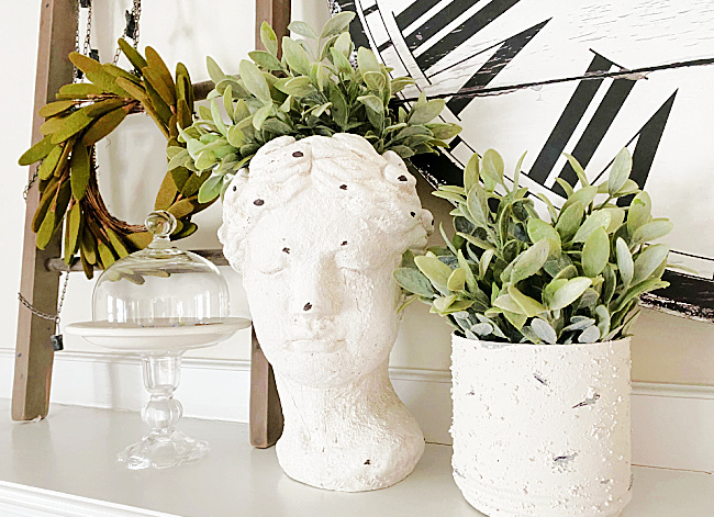 cement bust and planter on mantel