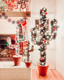 Three cacti in red pots lit up in white lights and colorful ornaments.