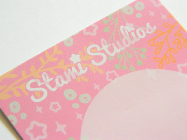 A photo showing the presentation card for a pin badge by the company Stami Studios. It is pink decorated with stars and plants in different colours