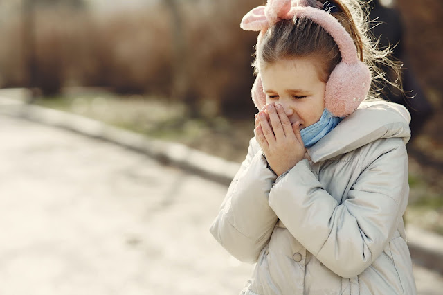 A young girl coughing on a street due to a sore throat