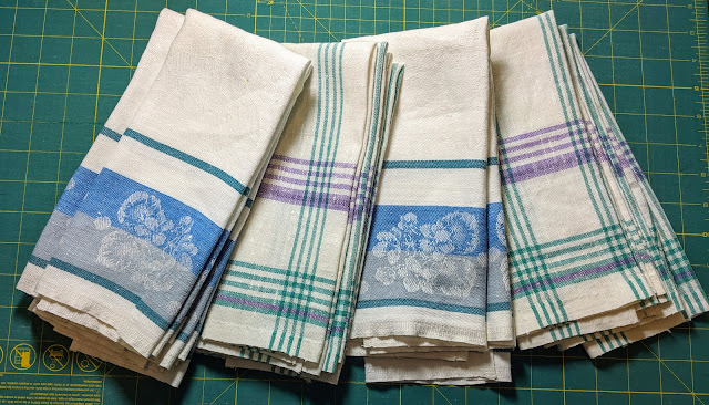 Two woven linens in medium blue on white. On has a wide blue and grey border with jacquard flowers banded with a narrow green stripe. The other is the same blue, grey, and green threads woven into a large, open plaid on the white background.