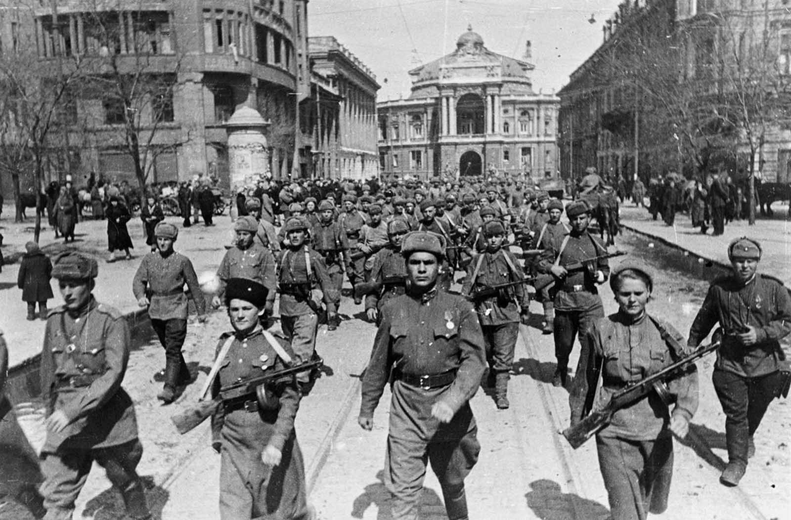 62nd Stalingrad Army on the streets of Odessa (The 8th Guard of the Army of General Chuikov on the streets of Odessa) in April of 1944. A large group of Soviet soldiers, including two women in front, march down a street.