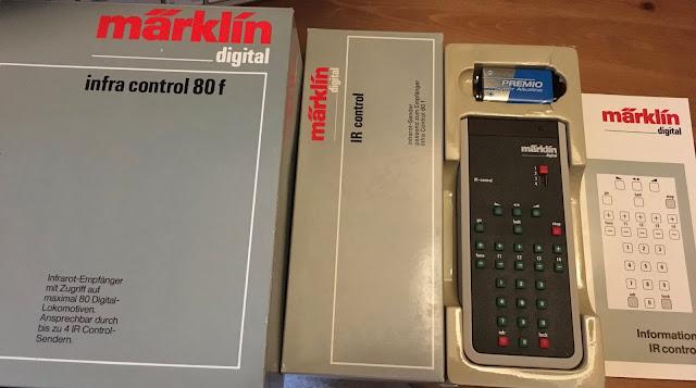 Links füllt das Bild die hellgraue Packung der infra control 80f mit dem roten Märkli Logo. Dann deutlich schmale die Packung der Fernbedienung IR control. Diese liegt geöffnet in einer Plastikschale daneben. Die Anleitung liegt ganz rechts.