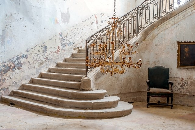 Stripped walls and stone staircase in foyer of French Chateau Gudanes