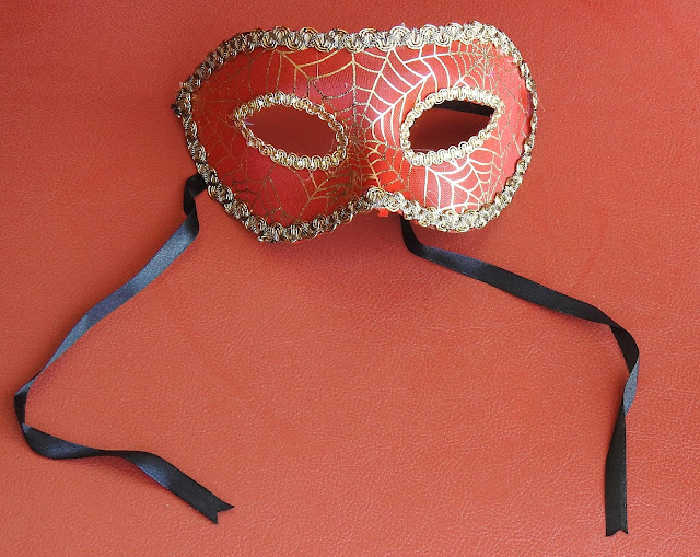 A masquerade style eye mask golden trim and a spiderweb design in gold.