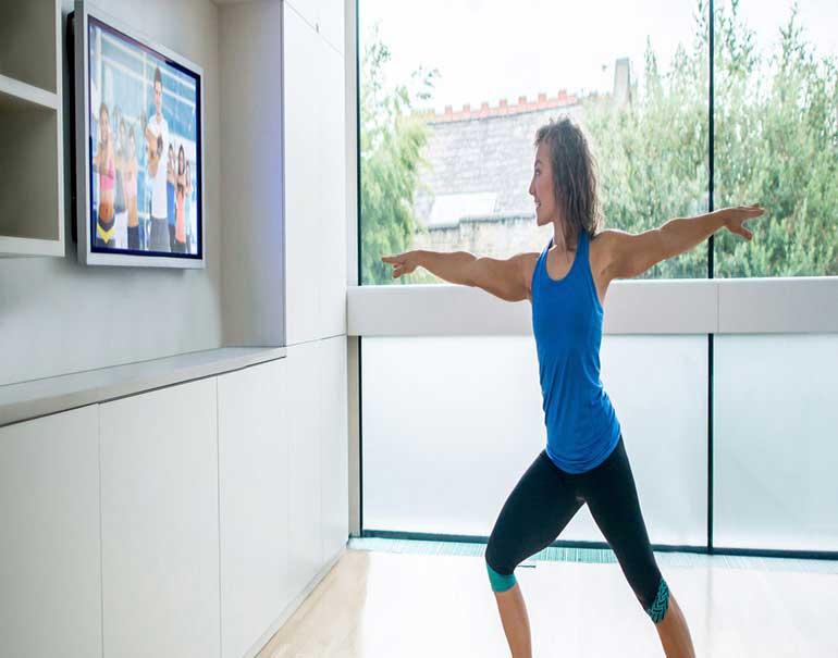 mulher fazendo exercício em frente a televisão