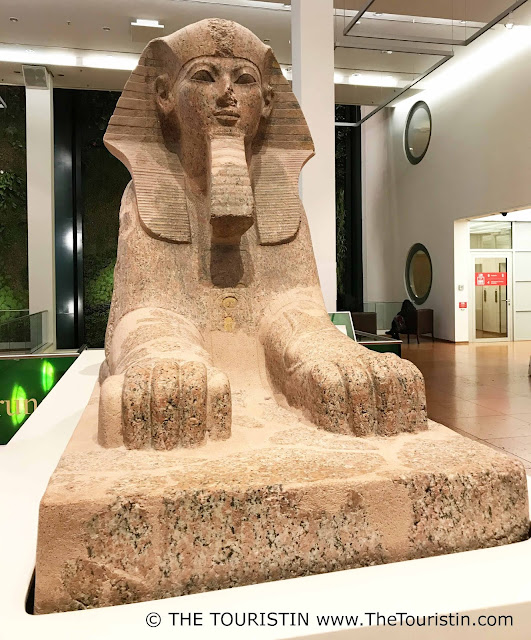 Giant sculpture of a 3,500 year old sphinx in the hallway of a bookshop..
