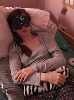 A caucasian woman in a dimmed room. She has an eye mask on and is holding a hot water bottle. She is laid in bed supported by pillows.