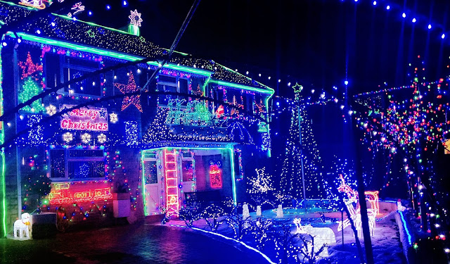 A house completely covered in Christmas lights and decorations of all shapes and sizes, the garden also has decorations all over it. It's very bright and a bit bonkers.