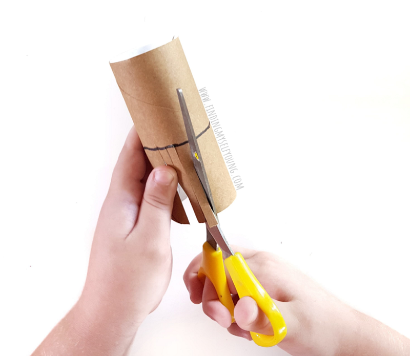 child cutting toilet paper roll