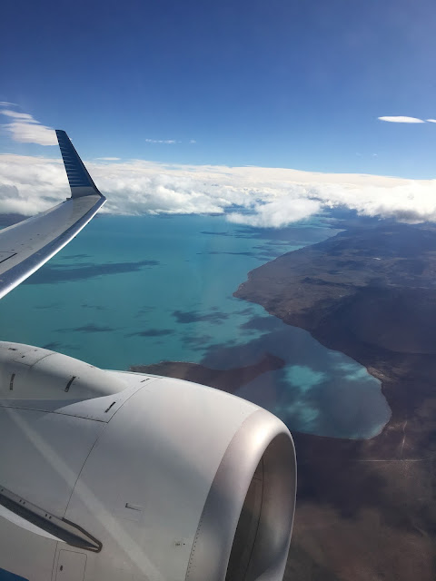 plane flying above arid plains and blue lakes