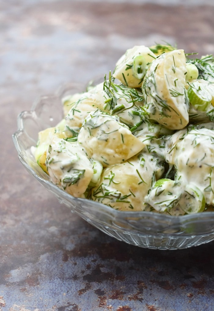 Close up of dill potato salad in a glass bowl