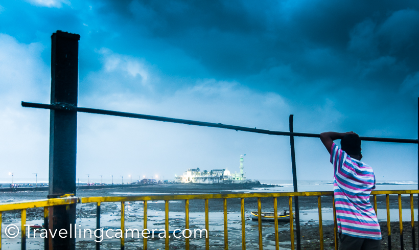 Last month I had a quick visit to Mumbai and explored some parts of the city with Desi Traveler. On the last day, we booked taxi and kept moving from one place to another. Haji Ali was one of the halts on our way. This Photo Journey shares more about Haji Ali Dargah in Mumbai, timings and some do's/don'ts.Haji Ali Dargah is located on shoreline and high tide area in Mumbai. The very first photograph of Haji Ali is clicked from the road where you need to park the car, if planning to visit the mosque. Please note that cameras are not allowed inside the Haji Ali dargah. At least I was stopped at entry gate and not carry camera inside. I dropped the idea of going beyond that point and came back towards the famous Haji Ali juice shop.I tried clicking Haji Ali Photographs from different places around the main road and most of the photographs are clicked with cell phone camera.There is also a famous Haji Ali Song, which remind me of this place now. And if you haven't yet listened to this song, go and check. I am sure you would love it.Haji Ali Mumbai is one of the main places to visit in the city. The Haji Ali Dargah was constructed in 1431 in memory of a wealthy Muslim merchant, Sayyed Peer Haji Ali Shah Bukhari, who gave up all his worldly possessions before making a pilgrimage to Mecca. Hailing from Bukhara , in present-day Uzbekistan , Bukhari travelled around the world in the early to mid 15th century, and eventually settled in present-day Mumbai. Check out more - The Dargah is built on a tiny islet which is located 500 meters from the coast and in the middle of Worli Bay. Haji Ali is in the vicinity of Worli . The edifice is a brilliant specimen of the Indo-Islamic style of architecture and I wish I could go closer to click some good photographs there. The islet is linked to the city precinct of Mahalakshmi by a narrow causeway, which is nearly a kilometre long.Haji Ali Mosque is clearly visible from a distance. This is the high tide area during evenings.Here is the famous Hai Ali Juice Centre which goes great business here. I noticed long queues of cars parked in front of this Juice centre and people order light snacks with fresh juices.It was getting dark. We spotted a tea vendor along the road and tried tea in Mumbai. Detailed experience of tea in Mumbai can be checked here I loved shooting Haji Ali in blue hour during monsoons. Isn't it best mood. Blue shades and a yellow boat to add appropriate color contrast.
