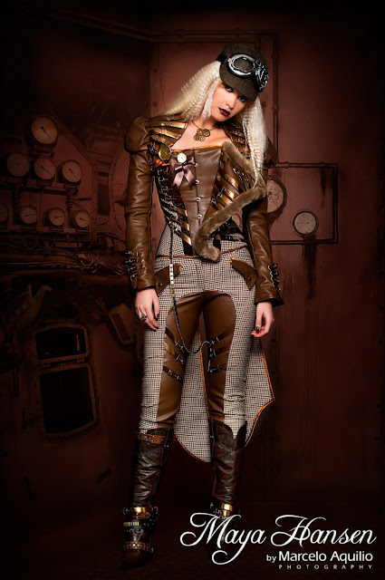 Woman wearing a 3 piece matching steampunk outfit: leather with fur trim corset, coat with tails, jodhpurs (riding pants) with tall brown leather boots. Hat with goggles, necklace with gears, pocket watch, rings.