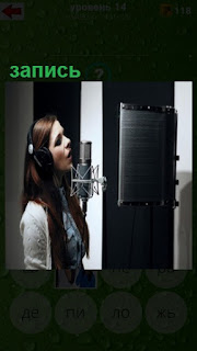 девушка перед микрофоном поет, происходит запись в студии