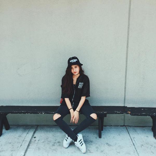 """Hà Lade cực """"cool"""" với cả cây đen từ mũ tai bèo cho đến áo và quần jeans. Điểm nhấn khác biệt trong set đồ của nàng hot girl Hà Nội là đôi giày sneaker trắng."""