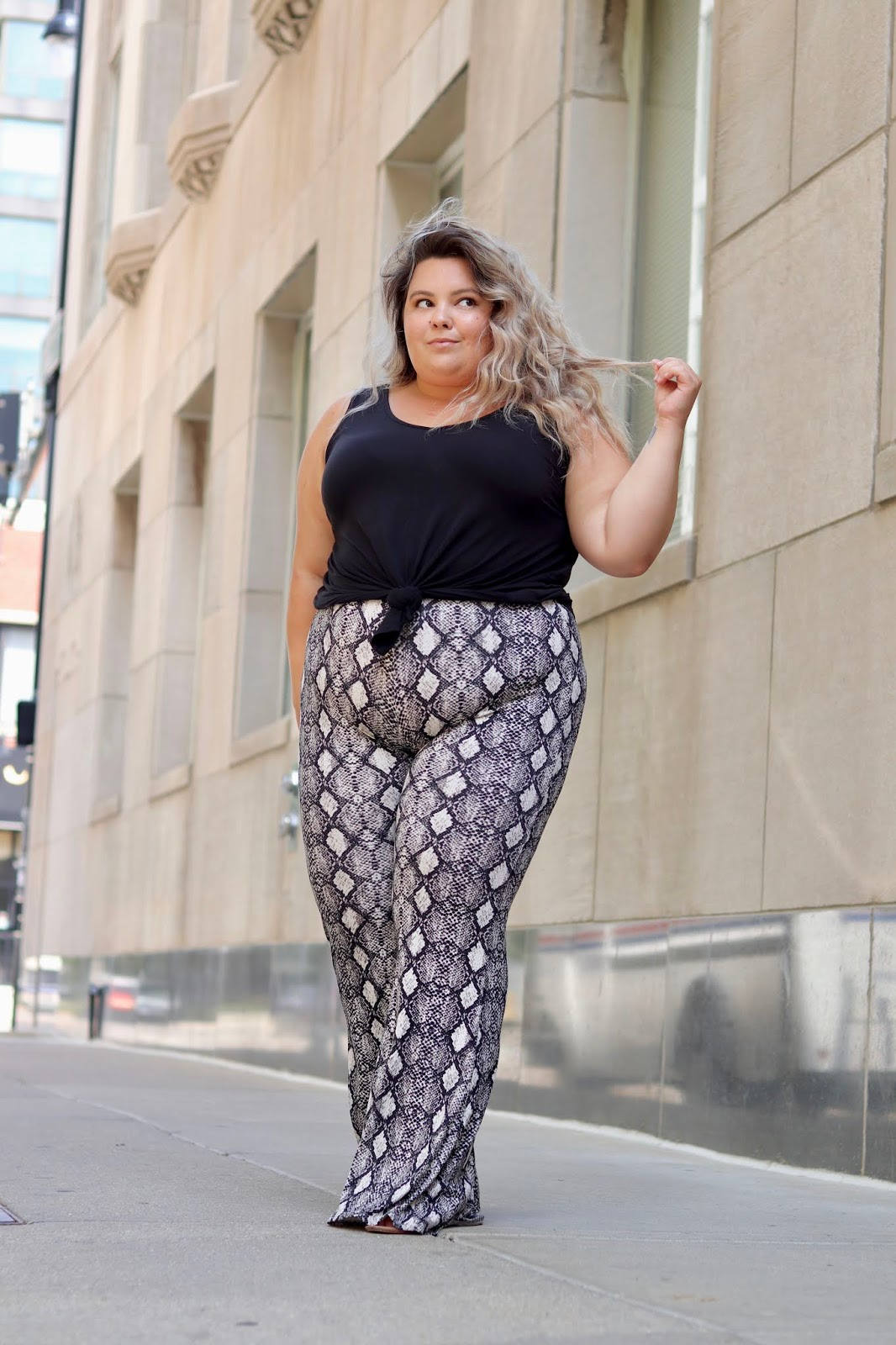 Chicago Plus Size Petite Fashion Blogger, influencer, YouTuber, and model Natalie Craig, of Natalie in the City, reviews Chic Soul's snake skin bell bottoms and basic black tank top.