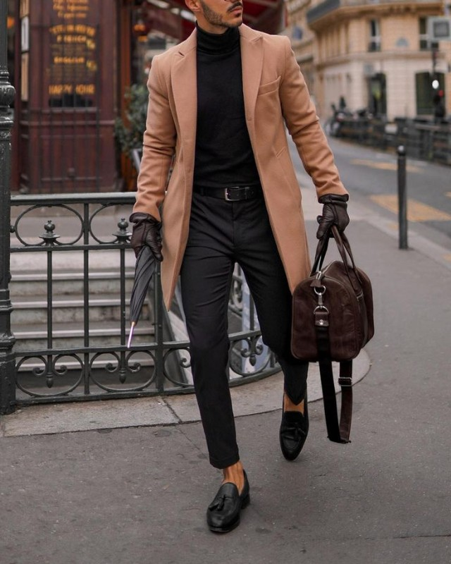 Man in long coat, high neck/turtle neck tee and trousers.