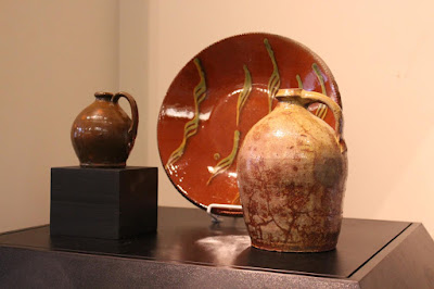 A small brown redware jug and a larger light colored jug on either side of a large orange redware plate with lines