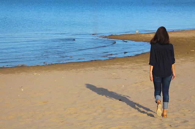 As Vantagens De Ser Solteiro, a imagem exibe uma mulher de costas caminhando na praia