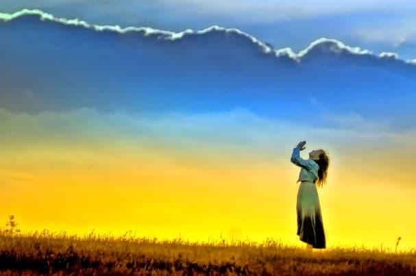 A imagem mostra uma jovem garota orando aos céus sob uma paisagem verde com um pôr do sol amarelado ao fundo.