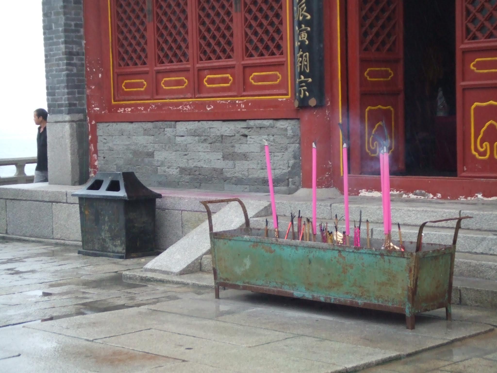 Mann geht entlang eines Tempels aus grauem Stein mit roter Tür und Fensterläden, die gelb abgesetzt sind. Rosa Räucherwerk in grünem Trog sowie schwarzer Mülleimer vor Gebäude.