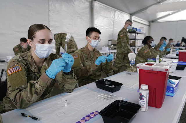 The US Army Medical Corps prepares a shot of the COVID-19 vaccine in Miami. Photo: AP