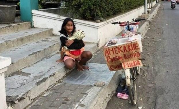 Tak Mau Mengemis, Bocah Yatim ini Pilih Berjualan Kue Sambil Gendong Adiknya