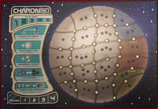 The game board for Charon Inc. Most of the board is a representation of a small moon, subdivided into twenty-one areas, all but one of which have one, two, or three eight-point star icons. The intersections of the borders have circle icons, and the midpoint of each side of each area also has a circle icon. The left side of the board has a number of other spaces; at the top of this section is the player order, with five numbered spaces. Below that are five spaces for special actions, from top to bottom: stolen intelligence, rare mineral find, engineering advance, synchrotron, and underground warehouse. At the bottom is another track, labelled 'round,' with four numbered spaces.
