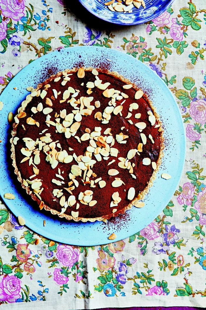 Chocolate Caramel Tart topped with cocoa and toasted almond slices on a pale blue plate