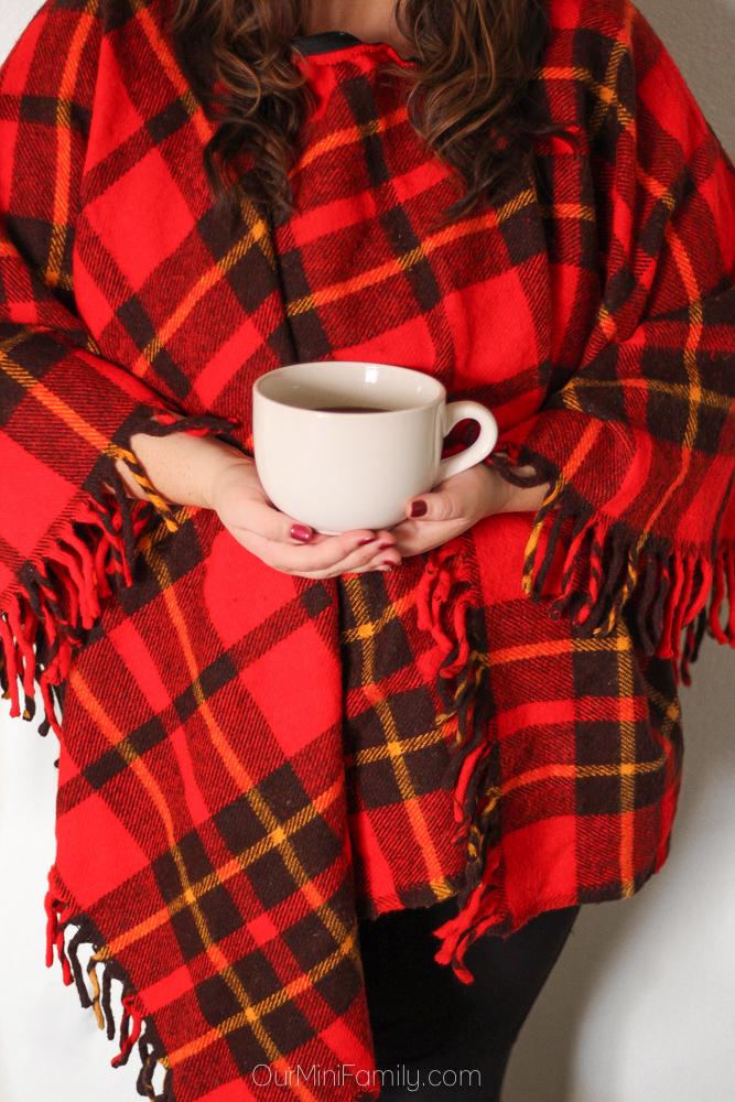 woman wearing buffalo plaid shawl holding bowl of soup