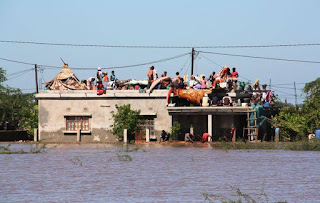 People taking refuge at the top of a building to escape the flood which has already claimed 66 lives.