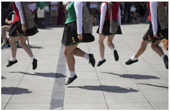Irlantilaistanssijain jalkoja ilmassa askeltamassa.