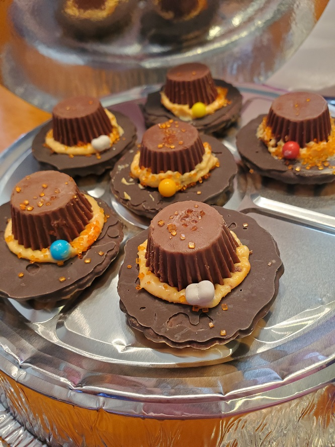 this is a tray of Pilgrim hats made with fudge stripe cookies and frosting with peanut butter cups in the center
