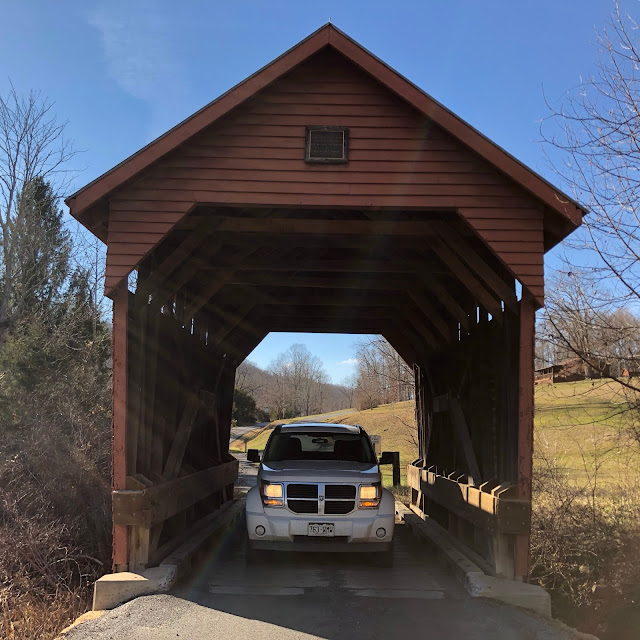 SUV going under covered bridge
