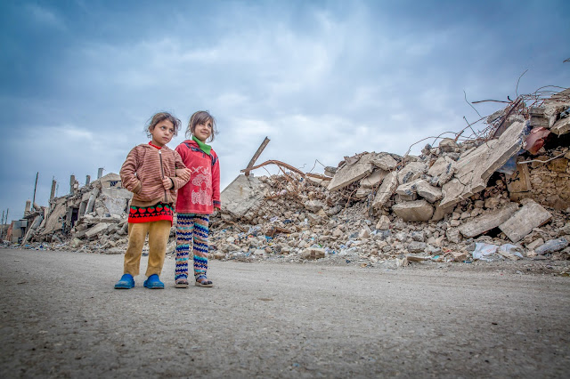 "Iraq, 2018: Noor and Sarah walk in the west of Mosul where many buildings have been totally destroyed. ""I do not know what happened to my father. He's been missing for three months,"" says Nour."