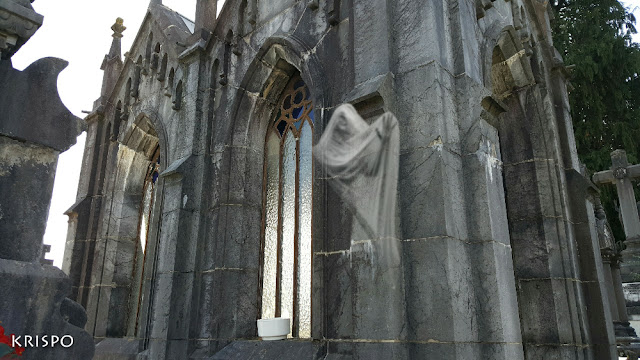 fantasma surgiendo de un panteon en el cementerio