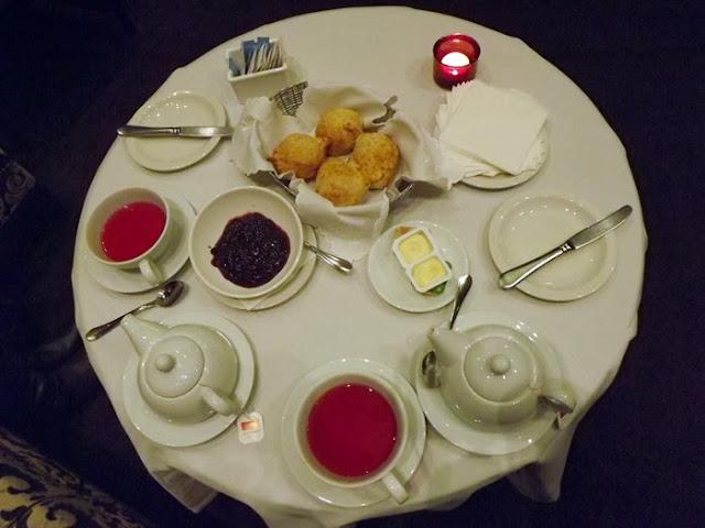 Mesa de chá das 5 com xícaras de chá, scones, manteiga e compotas