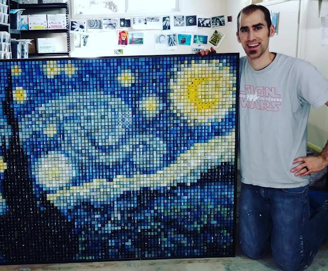 """El artista Erik Jensen arrodillado junto a una de sus obras. Erik lleva camiseta gris con las palabras Sign Wars y pantalón vaquero, Tiene el pelo corto, perilla y un anillo oscuro. La obra es un cuadro hecho de teclas de teclado de ordenador que imitan la obra """"La noche estrellada"""" de Van Gogh"""