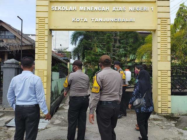 Polres Tanjung Balai Semprotkan Cairan Desinfektan Pada Sekolah & Fasilitas Umum