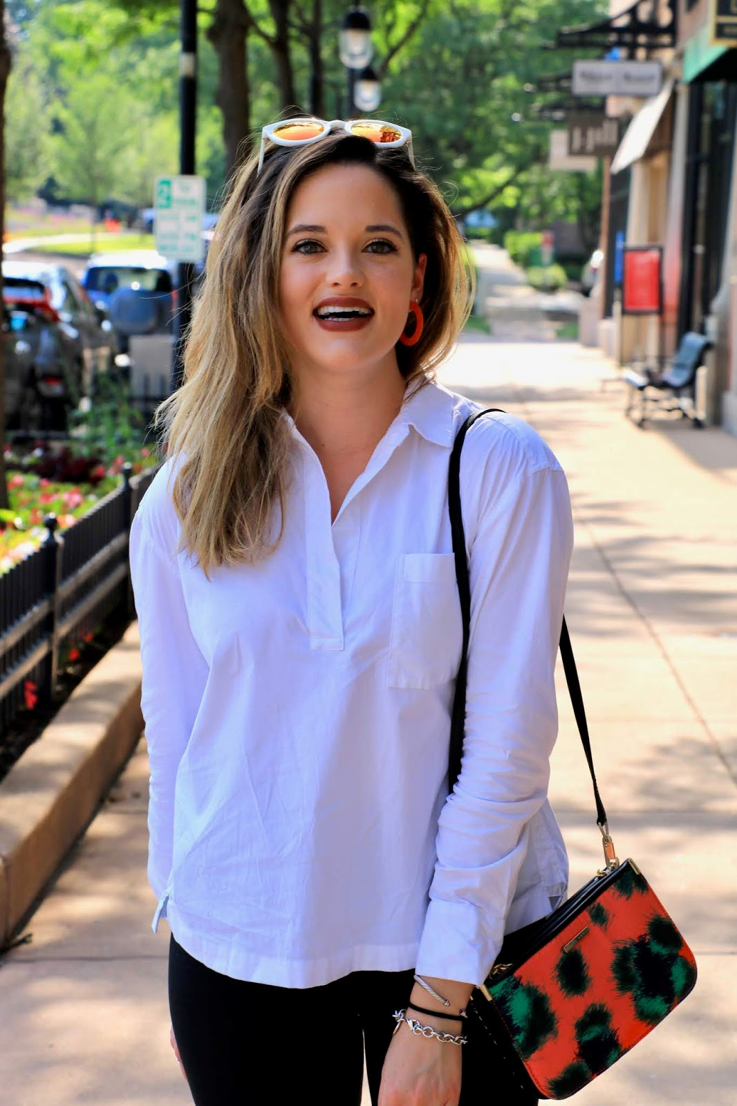 Nyc fashion blogger Kathleen Harper wearing a summer outfit of bike shorts and a white blouse.