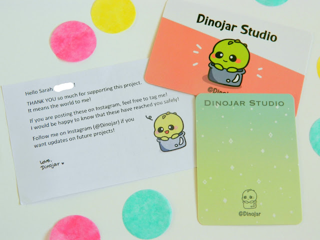 A photo showing a business card for Dinojar Studios, plus a thankyou note for backing their kickstarter project