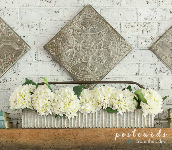 Faux white hydrangeas in a corrugated metal tool caddy on a wood mantel