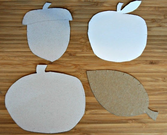 cardboard shapes of pumpkin, leaf, apple, and acorn