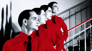 Imagen en blanco y negro de los cuatro componentes de Kraftwerk en fila india. Llama la atención que las idénticas camisas de sus integrantes son de color rojo con corbata negra