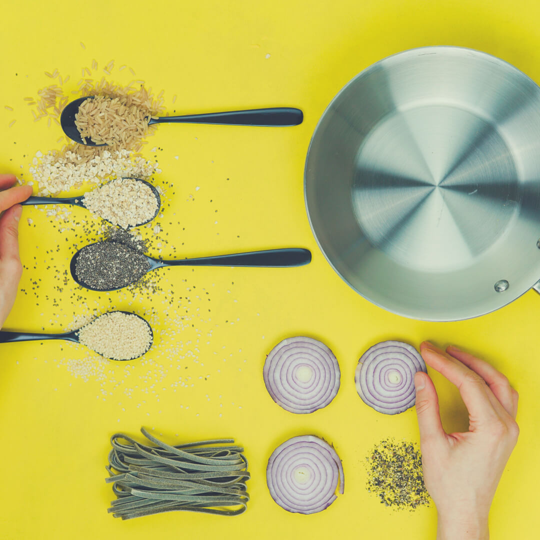 Spoons filled with pulses, sliced onions, and a silver frying pan sit on a yellow background.
