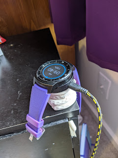 The watch sitting snugly in the charging cradle, which is lifted by the support.