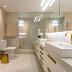 Banheiro com cores claras e detalhes dourados revestido com porcelanato!