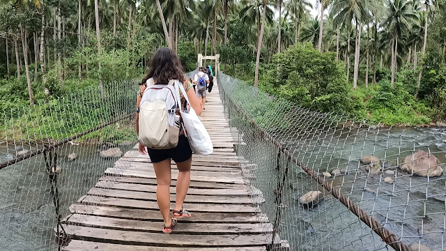 girl backpacker passing hanging bridge